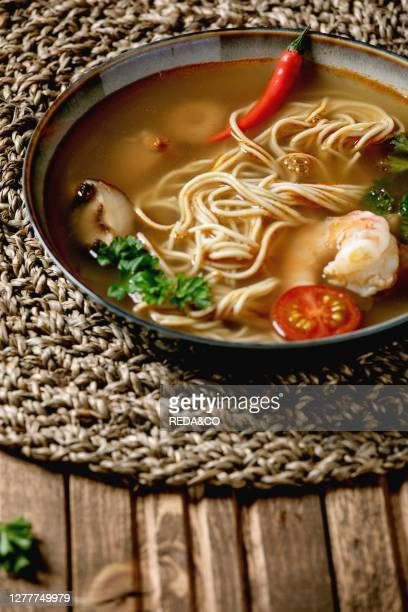 Asian spicy noodles soup with shiitake mushrooms and prawns. Ingredients above on straw wicker napkin over wooden plank table. Flat lay. Space. Asian...
