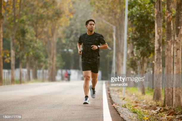 asian sportman jogging and checking smart watch between workout jogging outdoor - three wheeled pushchair stock pictures, royalty-free photos & images