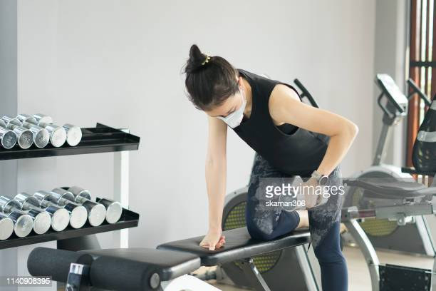 asian sporty female wearing anti pollution mask and workout weight training for keep fit with dumbbell  at gym - air respirator mask stock pictures, royalty-free photos & images