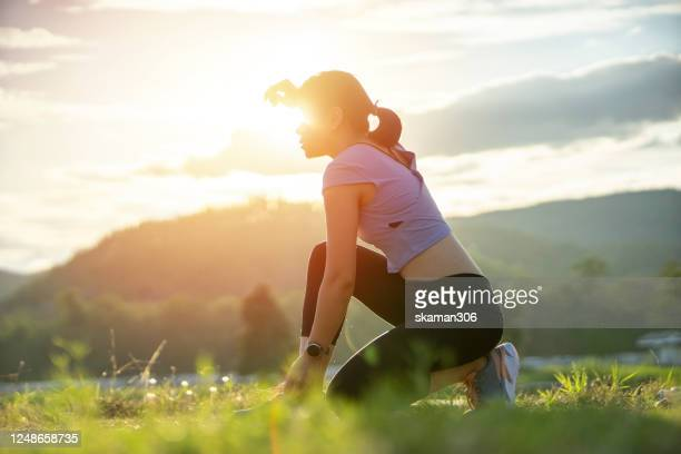 asian sporty woman running outdoor and exhausted and thirsty after finish workout  when unlock covid-19(coronavirus) control and start new normal life - コンセプト ニューノーマル ストックフォトと画像