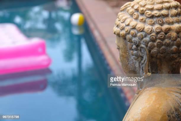 Asian statue and backyard pool