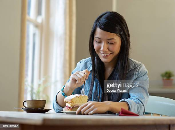 Asian student eating cake in coffee shop.