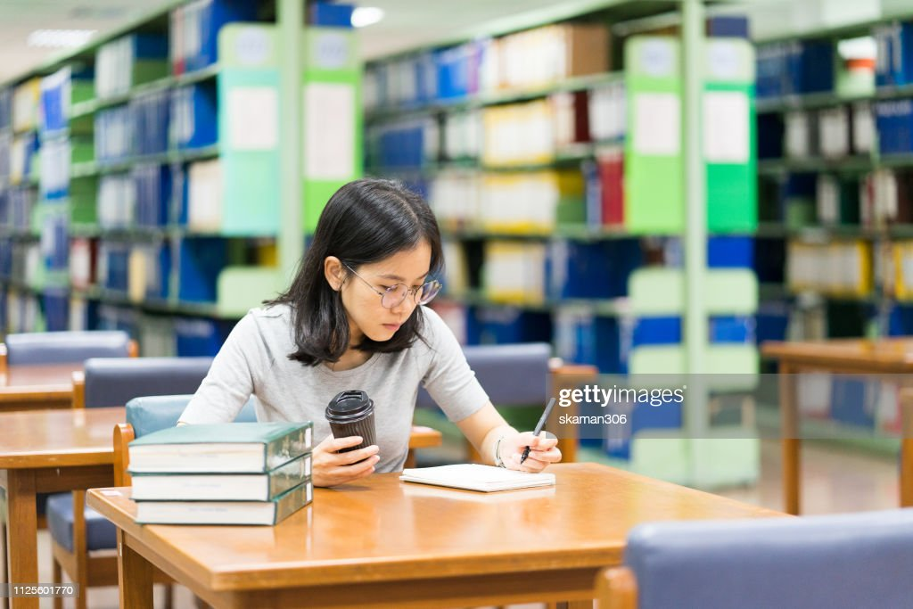 asian student feeling stressed and crazy with homework at library near university : ストックフォト
