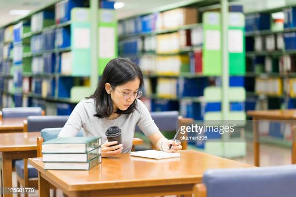 asian student feeling stressed and crazy with homework at library near university - very young thai girls fotografías e imágenes de stock