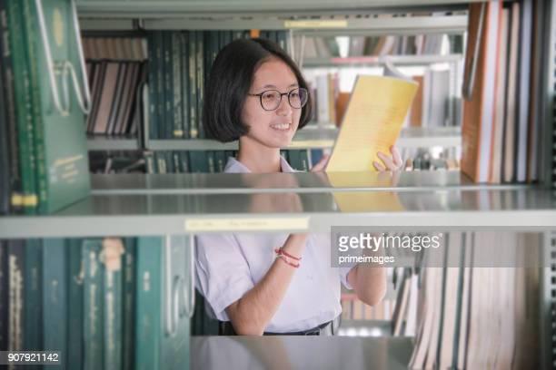 アジア学生の女の子は公共図書館で本を読んで