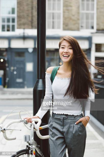 Asian Student Holding Bicycle Wind in Hair