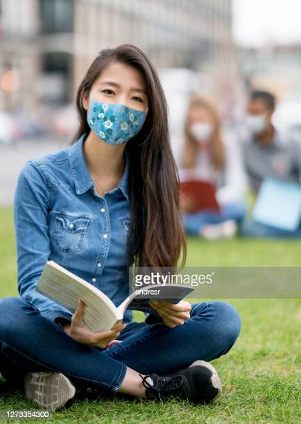 asian student studying outdoors wearing a facemask - university stock pictures, royalty-free photos & images