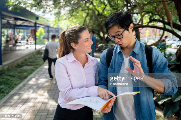 asian student talking to female teacher holding his notebook while she points at it and laughs standing at college campus - hispanolistic stock photos and pictures