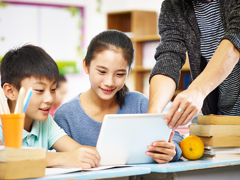 asian students getting help from teacher in class 859303718