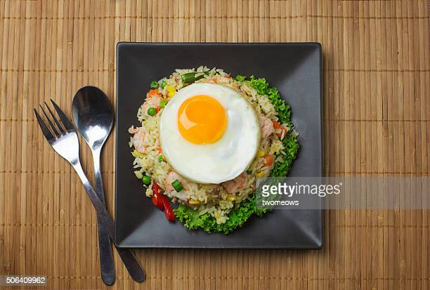 Asian style seafood fried rice with sunny side up egg on wooden kitchen counter top.