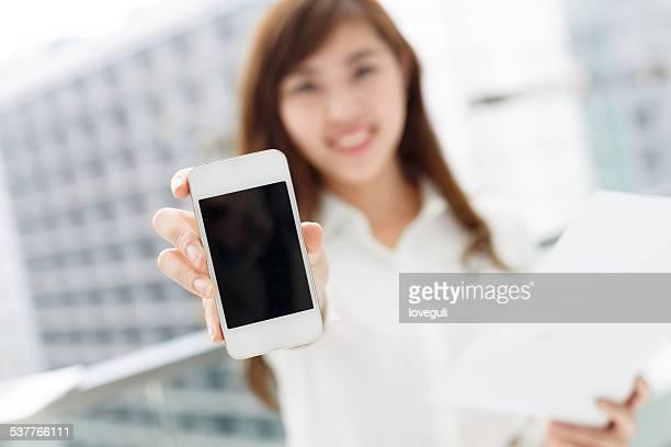 アジアのビジネスウーマンの成功は彼女のスマートフォンの表示でオフィスの廊下