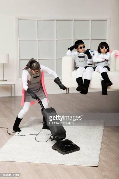 Asian superhero mother lifting sofa to vacuum underneath