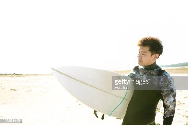 asian surfer at the beach - kyonntra stock pictures, royalty-free photos & images