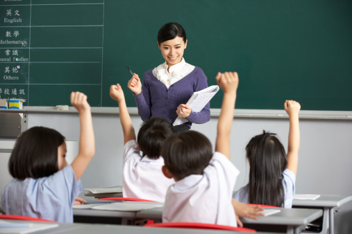 Asian teacher and students in classroom with arms raised 157689488