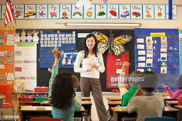 asian teacher teaching math to students in classroom - elementary school stock pictures, royalty-free photos & images
