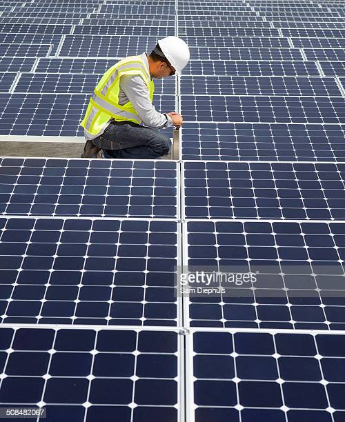 Asian technician working on solar panels