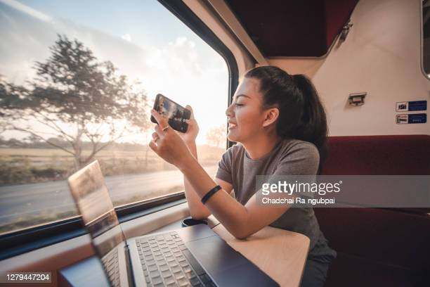 asian teen is a backpacker traveling by train, asia tourist woman take a photo by smart phone out the window with a notebook laptop on the table - travel foto e immagini stock