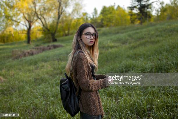 Asian teenage girl carrying backpack in field