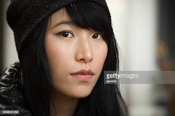 Asian teenage girl looking at camera with blank expression.