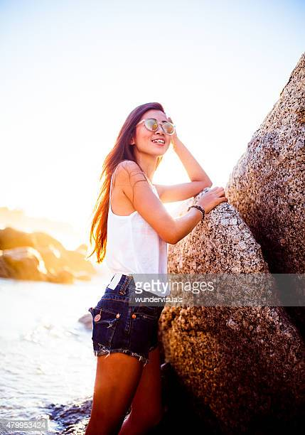 Asian teenage girl standing at the beach in summertime