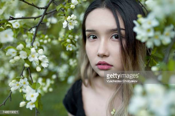 Asian teenage girl standing in branches with flowers