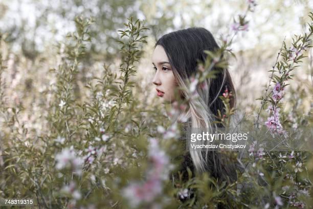 Asian teenage girl standing in flowers