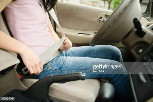 Asian teenager buckling seat belt