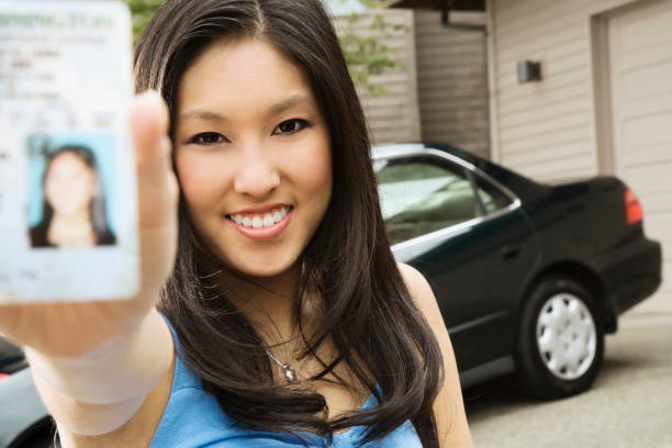 asian teenager proudly showing new driver's license - drivers license stock pictures, royalty-free photos & images