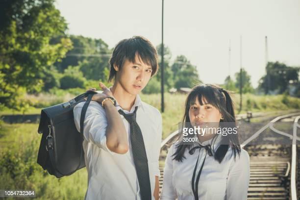 鉄道の線路の上に立って学校の制服でアジアの 10 代 - 制服 ストックフォトと画像