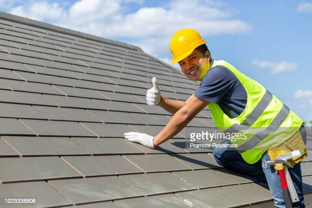 asian tile roofing workers, smiling at the camera, lifted their thumbs to indicate the stability of the roof. - herpes zoster fotografías e imágenes de stock