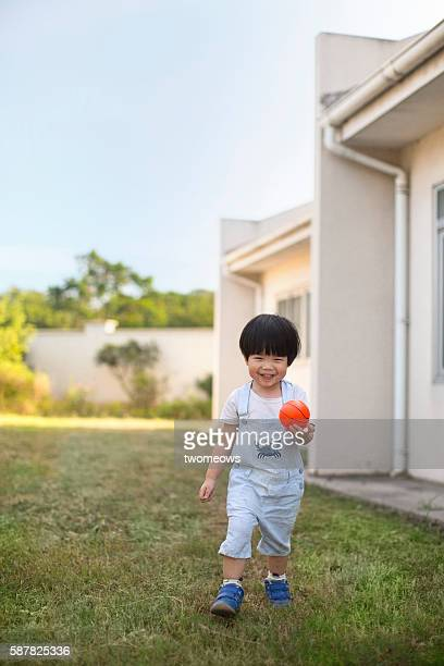 Asian toddler 2 to 3 years boy playing kicking ball in the garden.