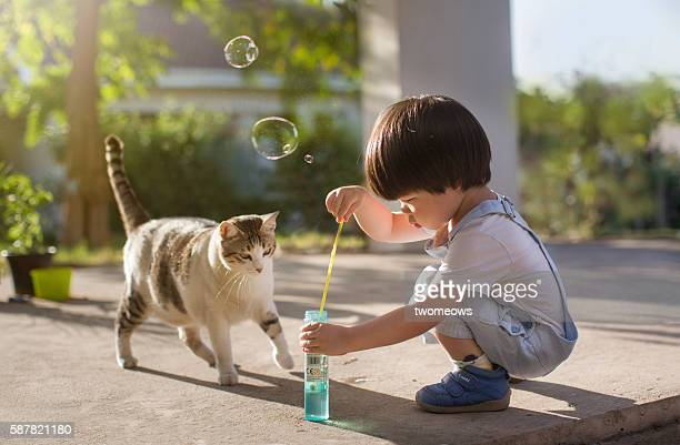Asian toddler boy 2 to 3 years old making bubbles in the garden.