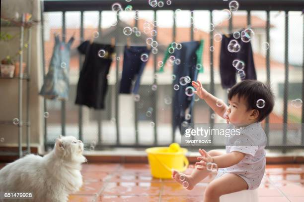 Asian toddler boy catching soap bubble.