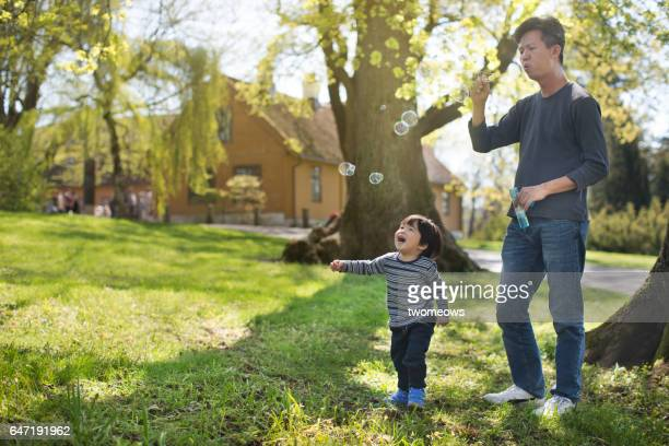 Asian toddler boy chasing bubbles in green open space.