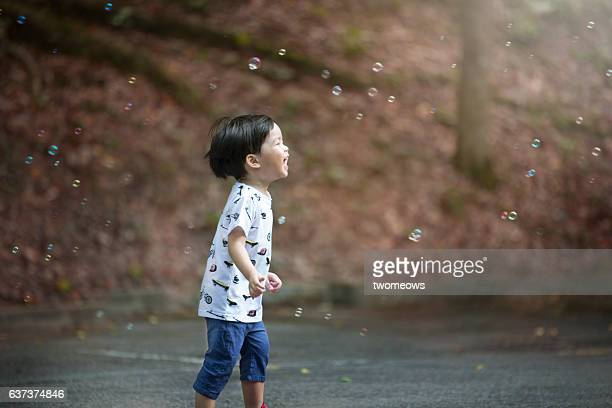 Asian toddler boy chasing soap bubble.