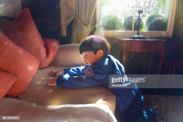 Asian toddler boy curious with lights reflected by chandelier.