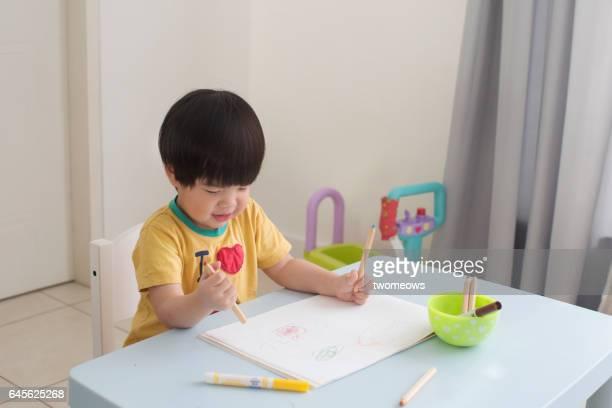 Asian toddler boy doodling at home.