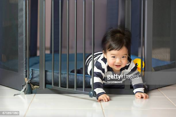 Asian toddler boy escaping from play pen.
