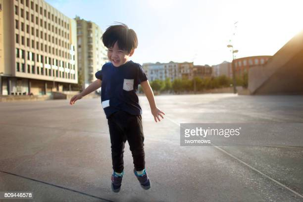 Asian toddler boy jumping in a public square empty space.
