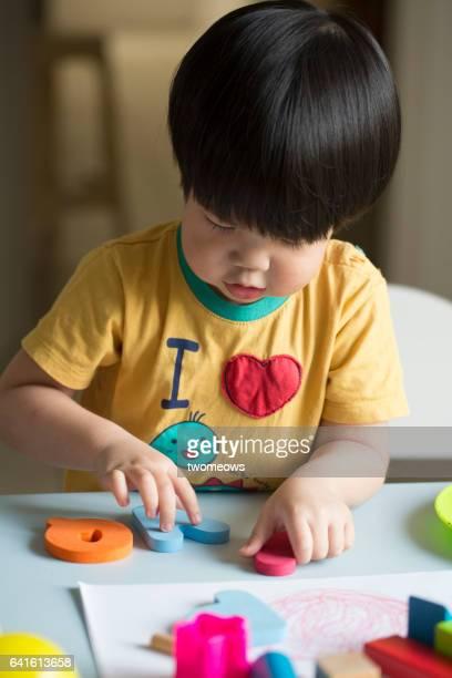 Asian toddler boy learning alphabet.