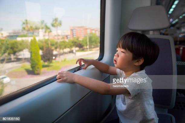 Asian toddler boy looking at view through train's window.
