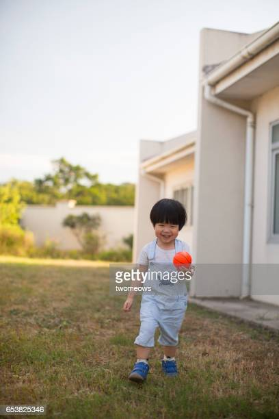 Asian toddler boy playing ball in backyard.