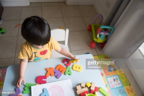 Asian toddler boy playing with alphabet.