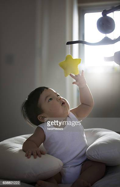 Asian toddler boy reaching out to catch a rotating toy star.