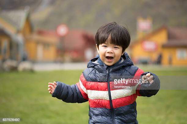 Asian toddler boy running.