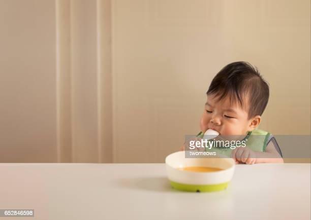 Asian toddler boy tasting food.