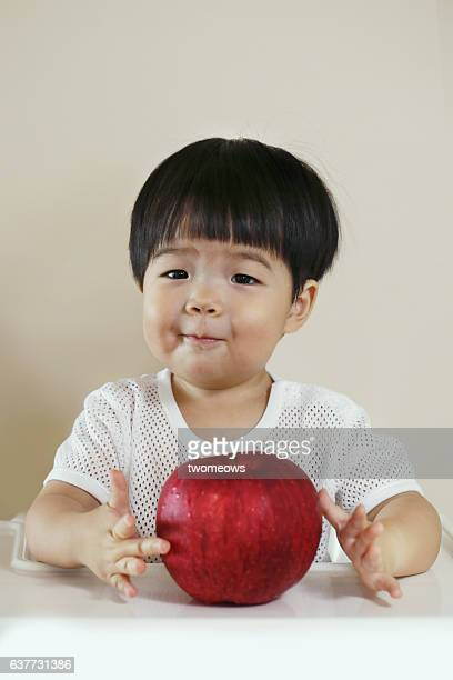 Asian toddler boy with an big apple.