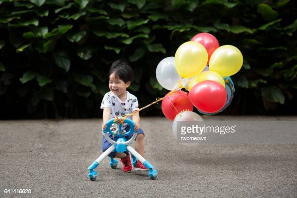 Asian toddler boy with balloons.
