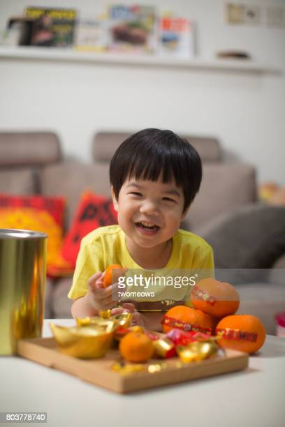 Asian toddler boy with Chinese new year food and drink.