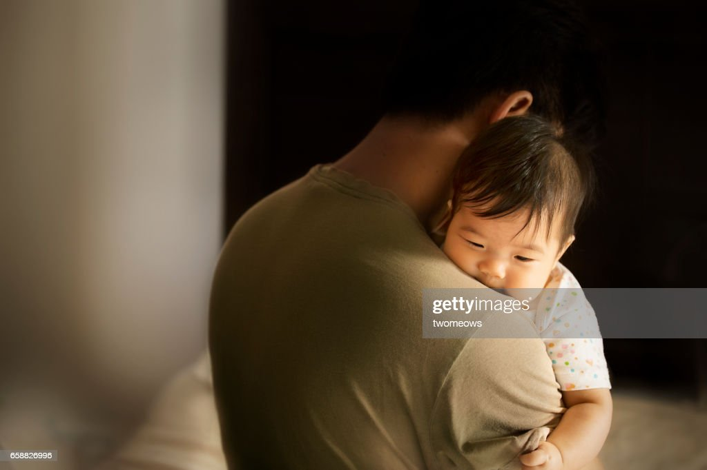 Asian toddler carried by father in moody bedroom background. : Stock Photo